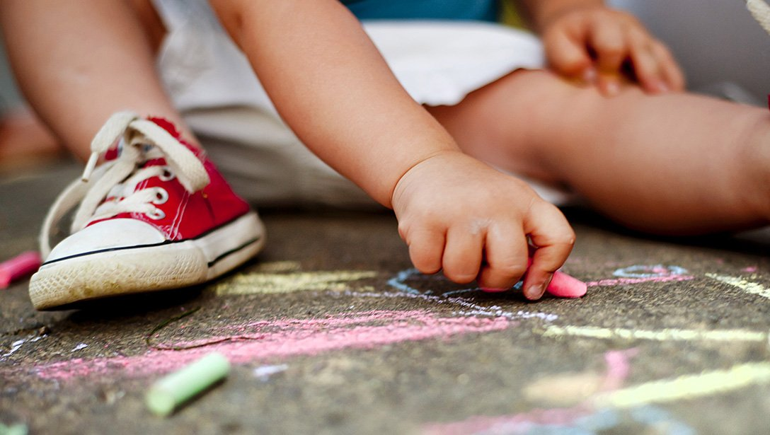 toddler chalk drawing with red shoes