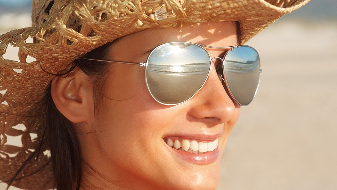 Women smiling while wearing a straw hat and sunglasses.